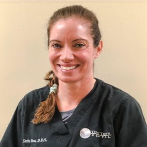 A female dentist with brown hair braided to the side smiling and standing in front of a beige wall
