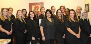 A group of women standing and smiling in front of a dental office